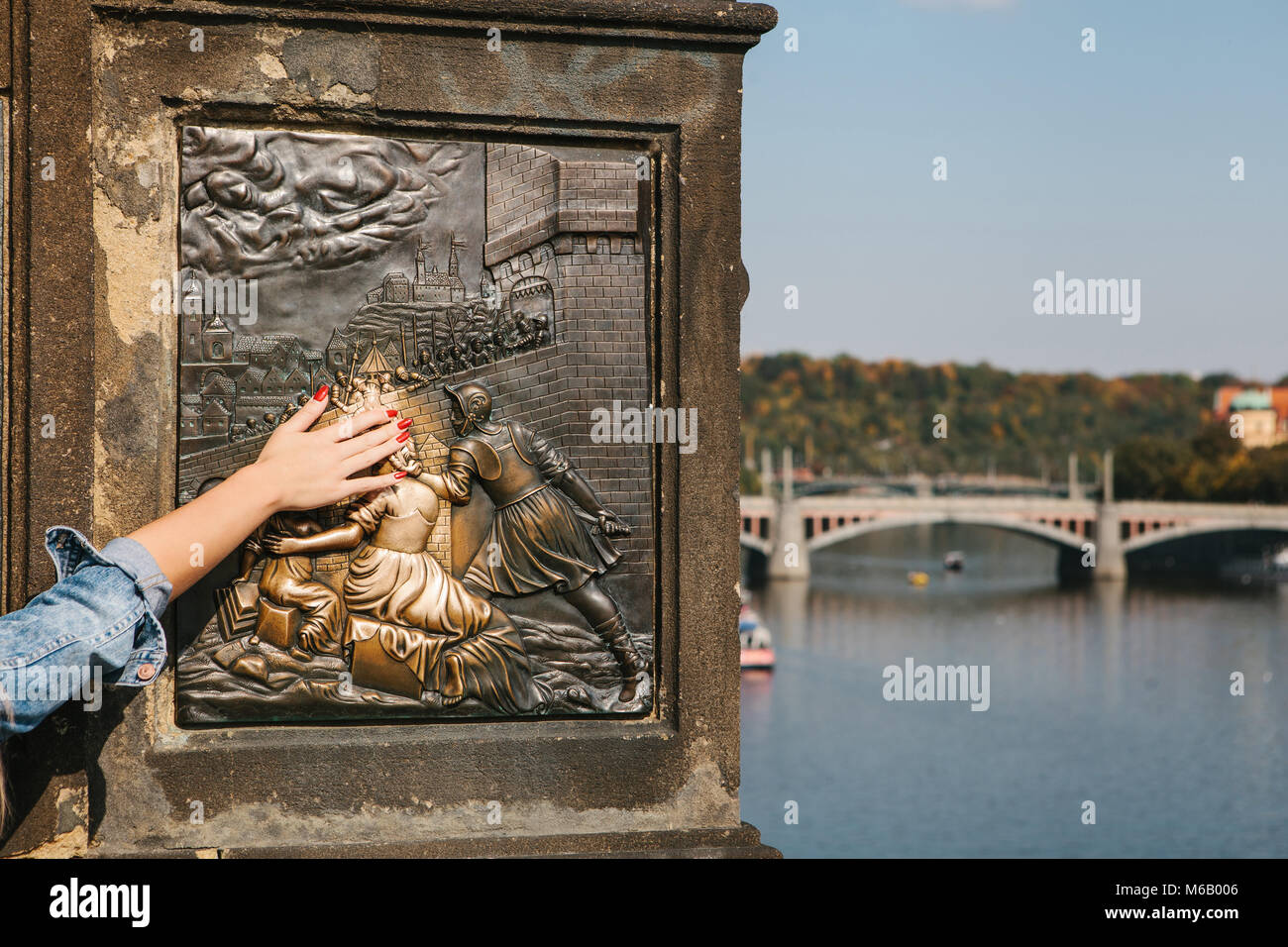 Woman tourist touches a bronze statue of John of Nepomuk on the Charles bridge in Prague, Czech Republic for good - Stock Image