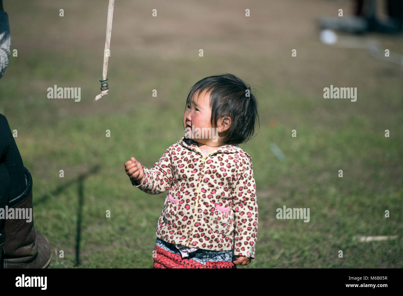 A young nomadic Mongolian girl is fascinated by a rope. Gorkhi-Terelj National Park, Mongolia. - Stock Image