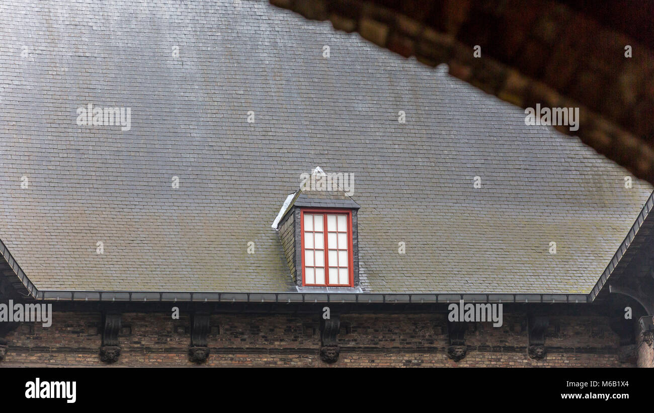 The Belfry's inner courtyard's massive tiled roof with a solitary dormer window towering over the open courtyard Stock Photo