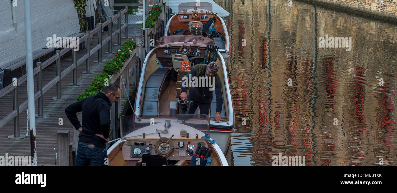 Three Bruges tourist canal boats being prepared for the first of many trips around the beautiful medieval city's - Stock Image
