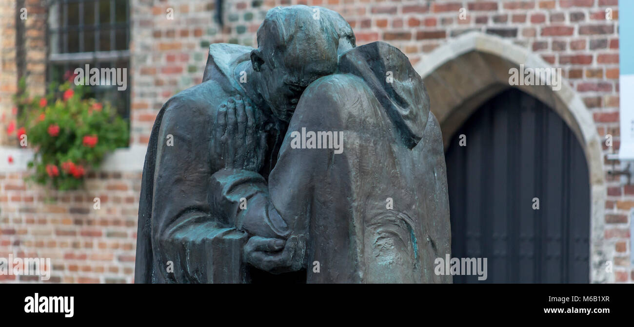 Pax, Two monks embrace,one old one young,This statue sculptured by Octave Rotsaert can be found in the courtyard - Stock Image