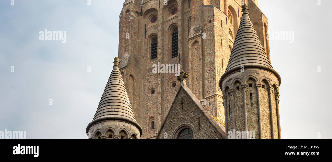Two conicle brick spires of the Church of Our Lady  foreground the church's magnificent tall tower - Stock Image