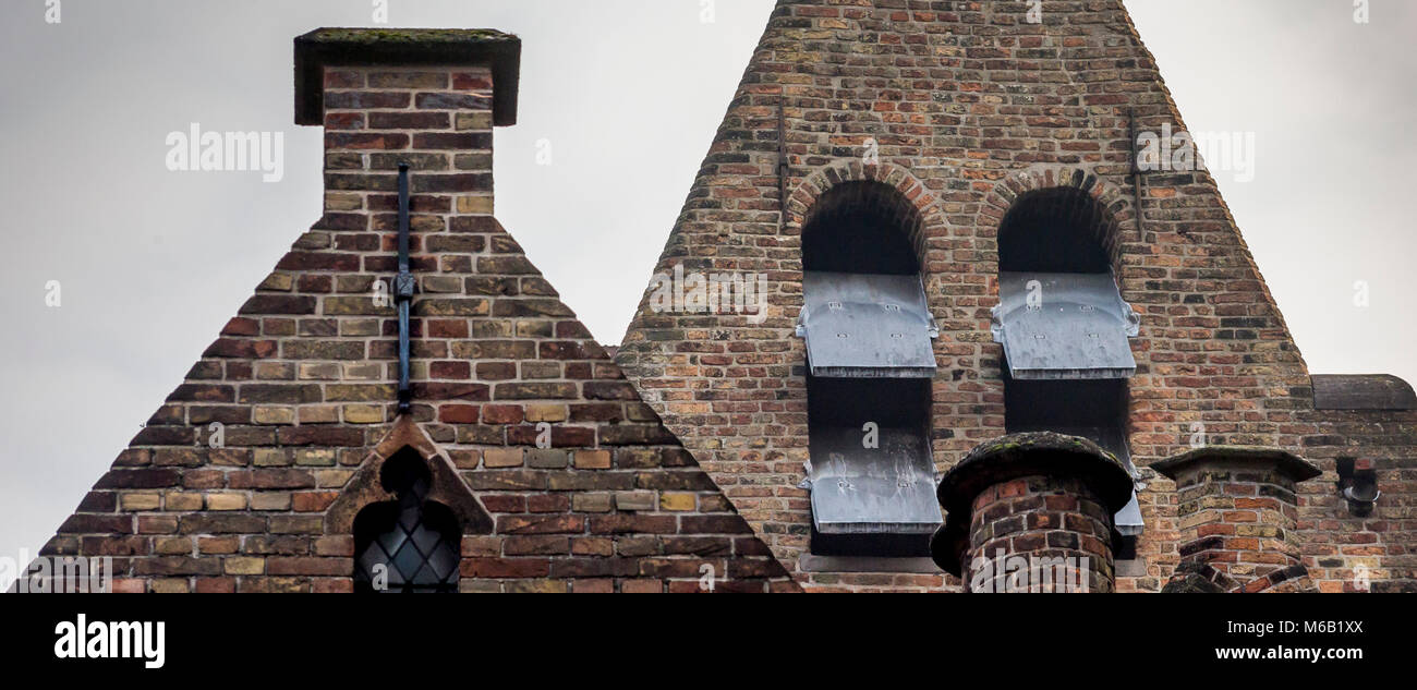 Triangular shaped ornate Flemish architectual brickwork skylined in the famous city of Bruges - Stock Image