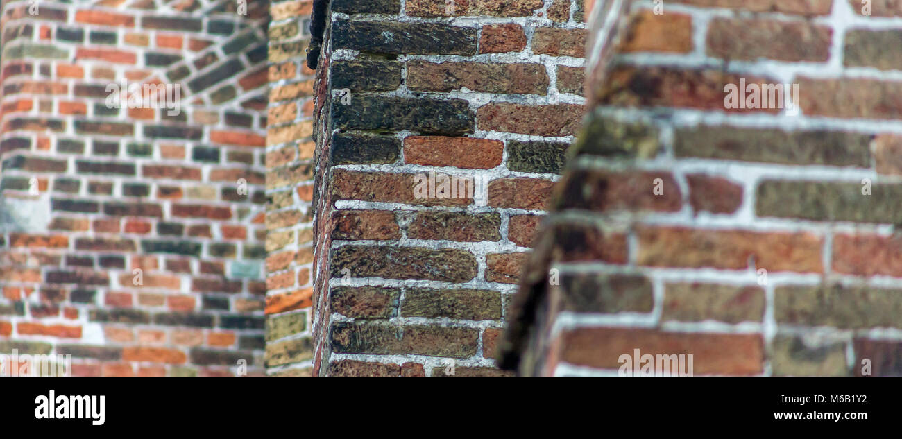 Brickwork exampling the many different types of architecture in the ancient medieval city of Bruges - Stock Image