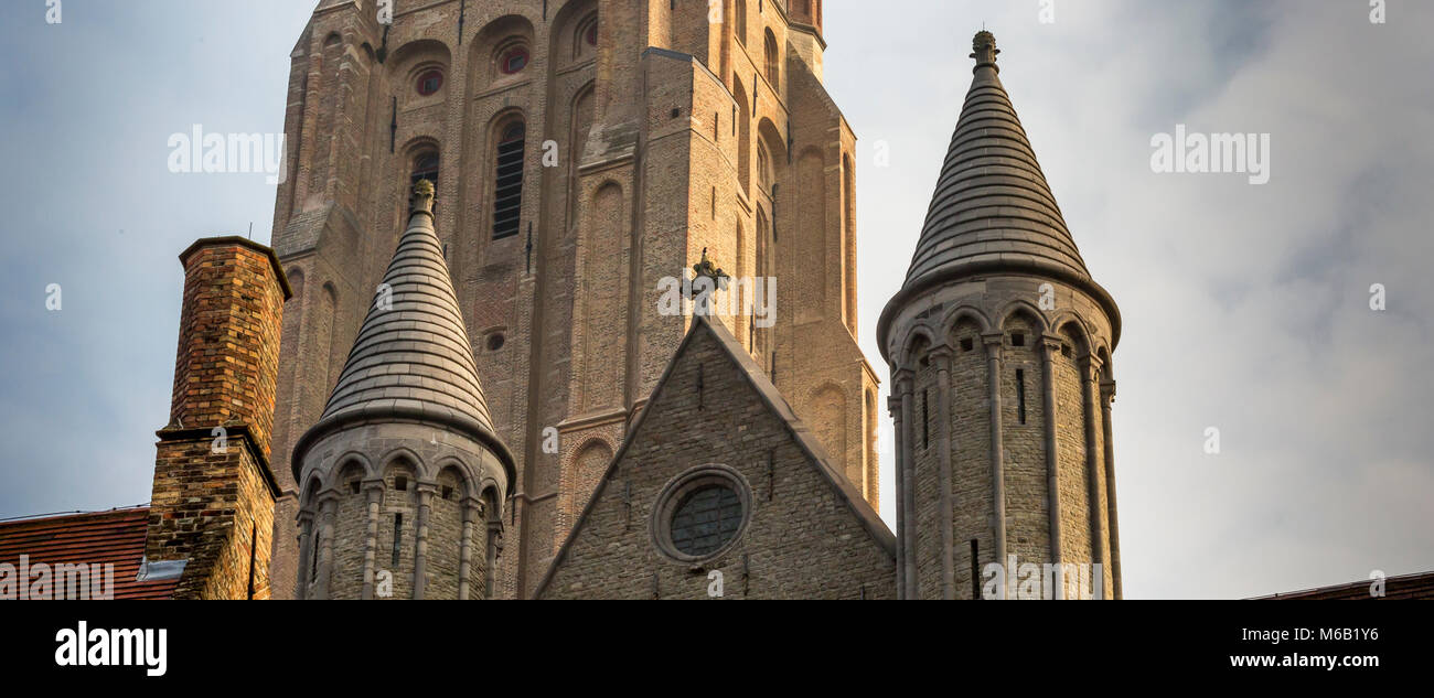 Two conicle spires and an ornate brick chimney of the Church of Our Lady  foreground the church's magnificent - Stock Image