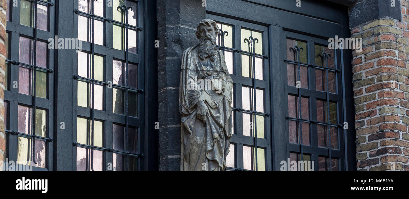 Religious stone statue situated in the courtyard of St John's Hospital in Bruges - Stock Image