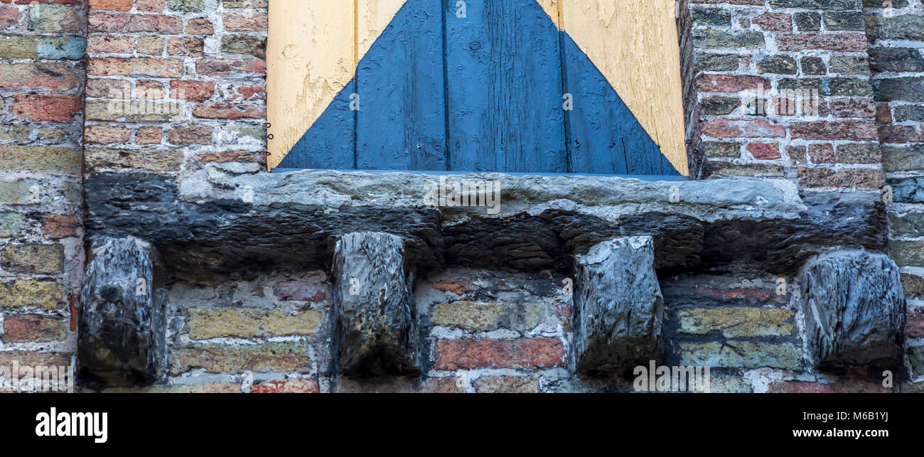 Ornate hand carved stone corbels adding structural support on an ancient medieval building's brick window frame - Stock Image