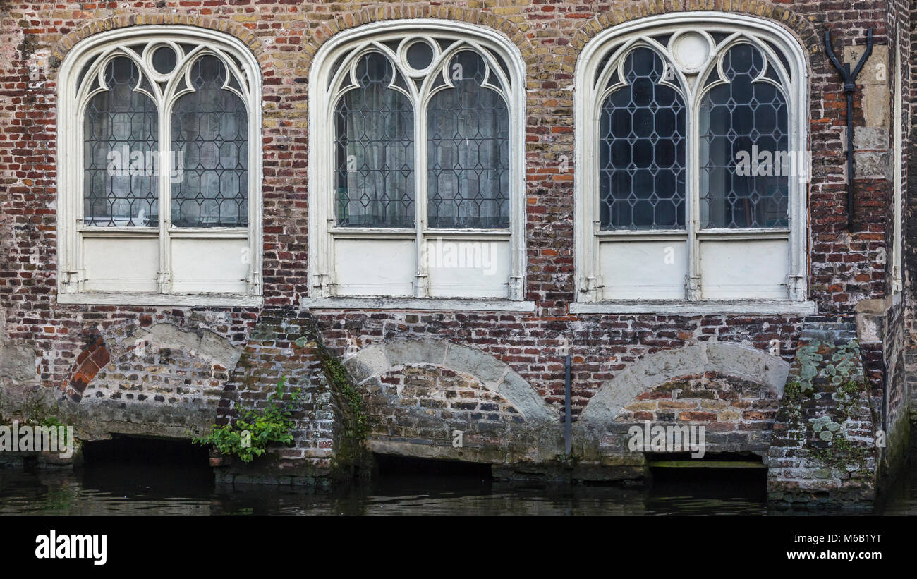 Three ornate stone carved arched windows on an ancient house on the magnificent canal waterway system in the heart Stock Photo