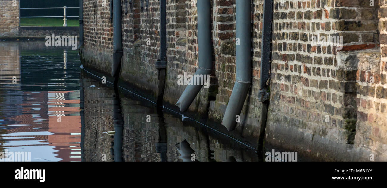 Rain downpipe spouts fixed onto ancient brickwork surrounding the canal in Bruges - Stock Image