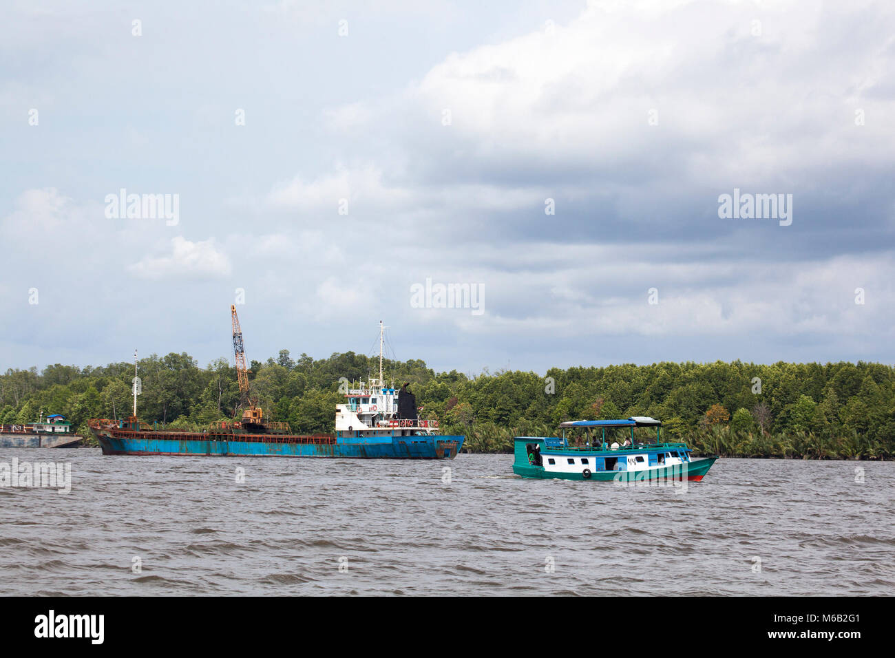 Klotok, a traditional river boat on the Kumai River leaving the port of Kumai in central Kalimantan, and industrial - Stock Image