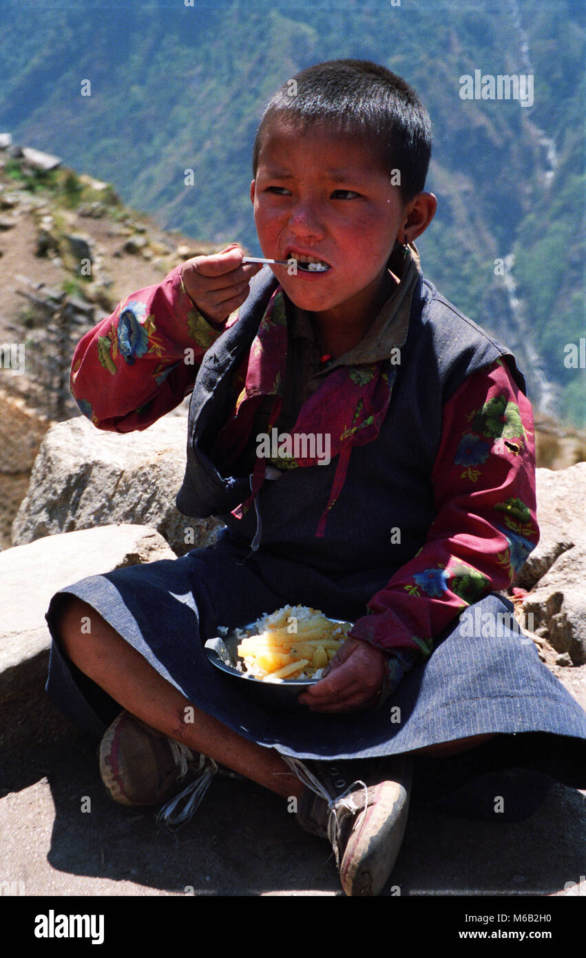 A young Nepali girl eating Dhal Bhat with veggies. - Stock Image