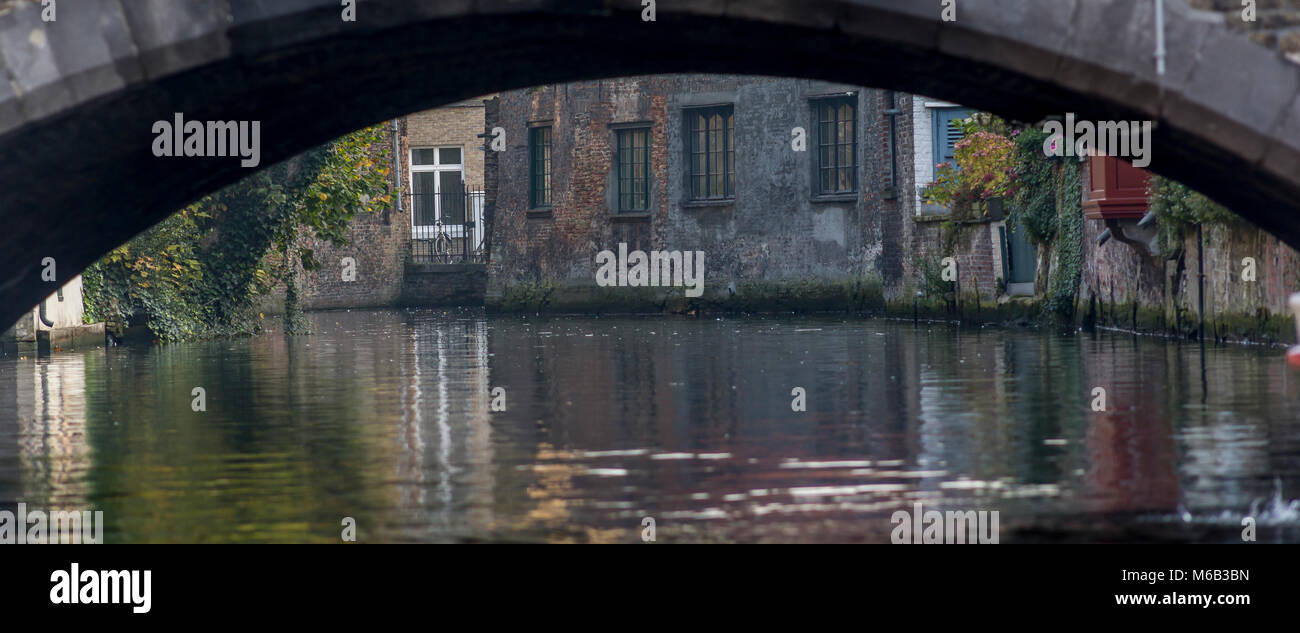 A  view through a Bruges bridge where the buildings are reflected in the  calm water of the busy waterways canal Stock Photo