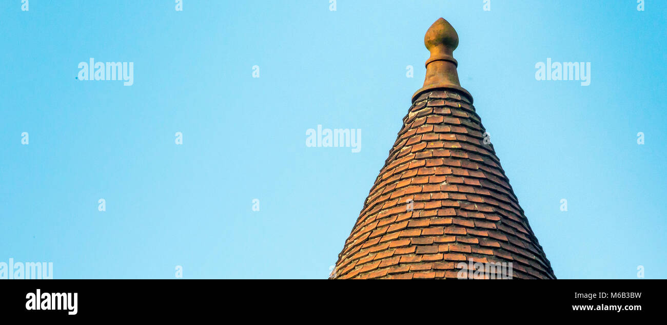 Conical clay tiled spired roof of the Church of our Lady in the Medieval City of Bruges against a blue October sky - Stock Image