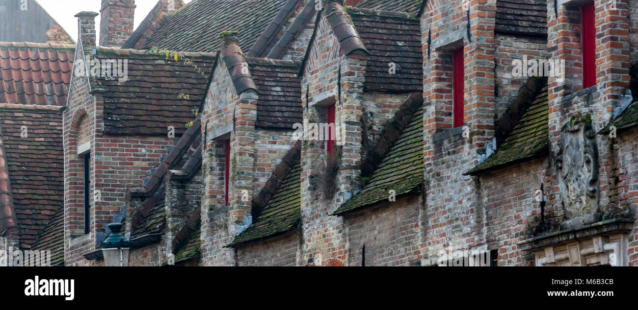 Ancient brick Bruges roofline with five Gothic walled dormer windows overlooking the city's canal Stock Photo