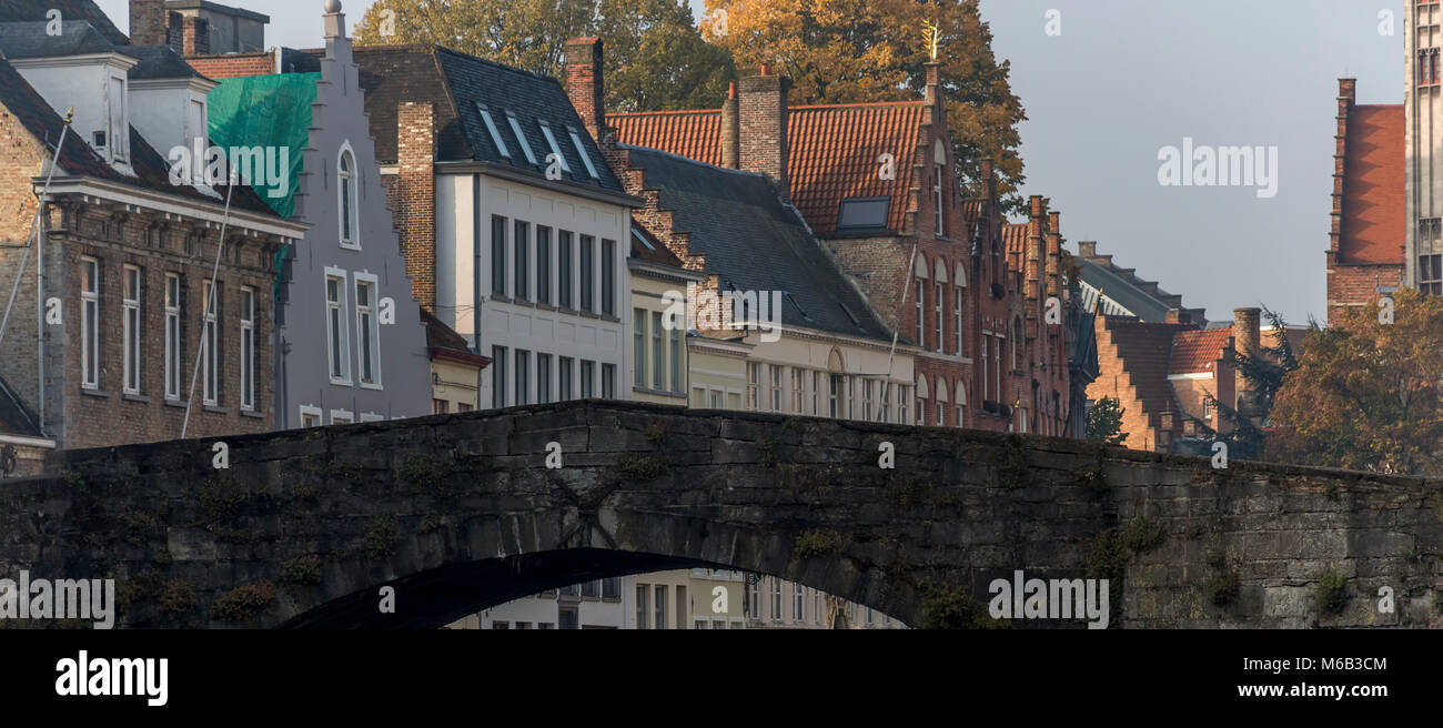 Brick Bruges bridge on the canal with grand ornate architectural designed homes along the banks overlooking the - Stock Image