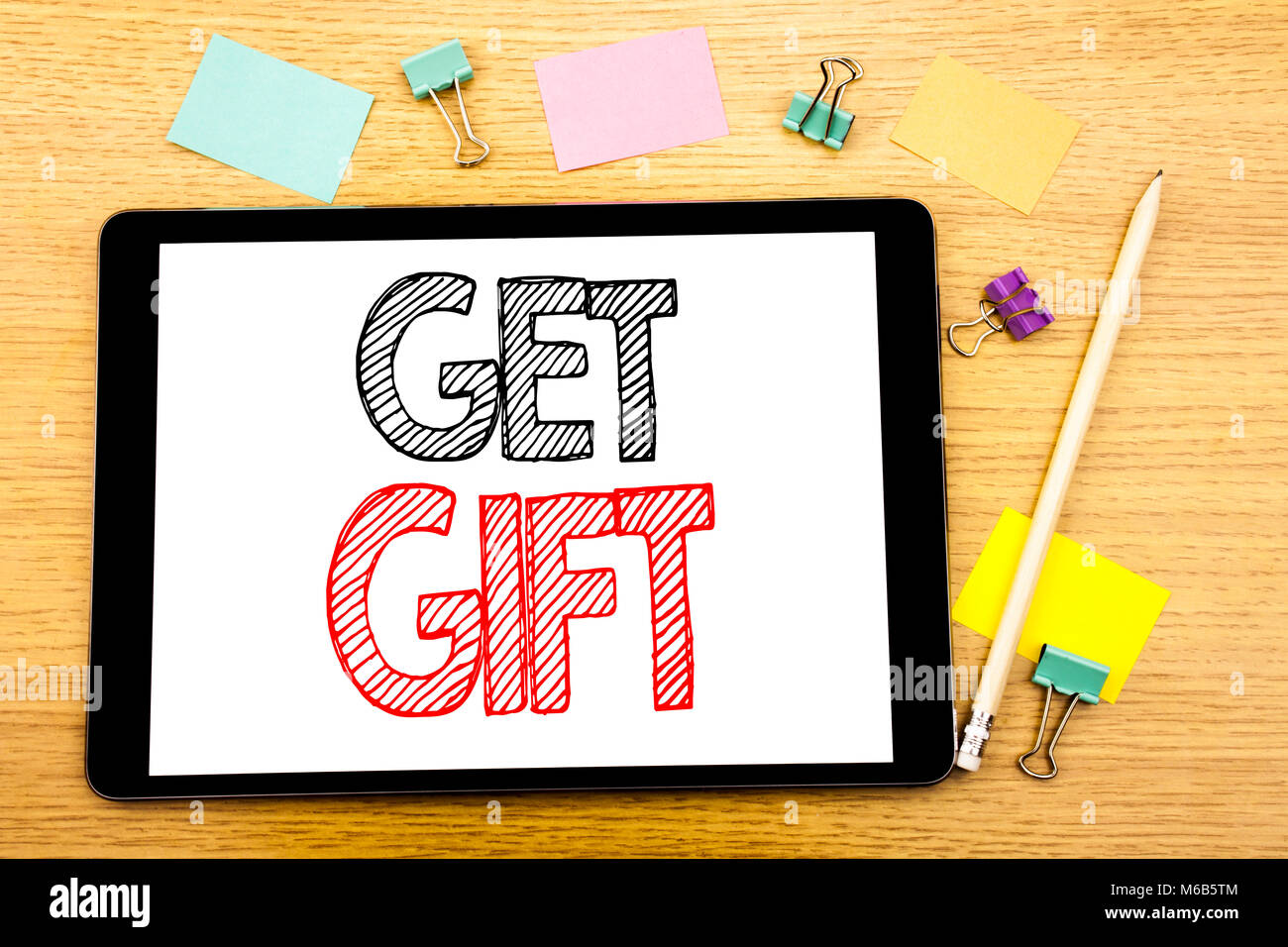 Writing text showing Get Gift. Business concept for Free Shoping Coupon Written on tablet, wooden background with - Stock Image