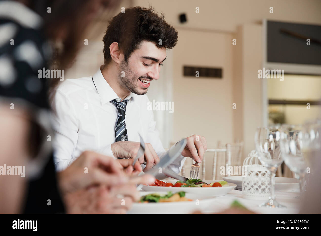 Close up shot of wedding guests talking while enjoying the starter of their meal at a wedding. - Stock Image