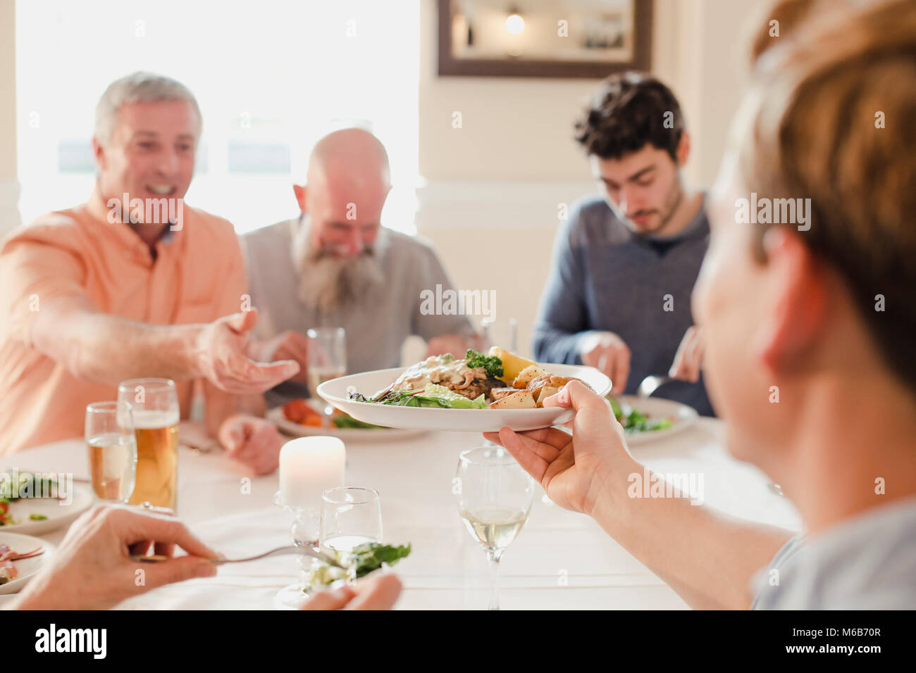 A table of male guests are eating at a wedding dinner together, One of the men is passing his plate to someone else - Stock Image