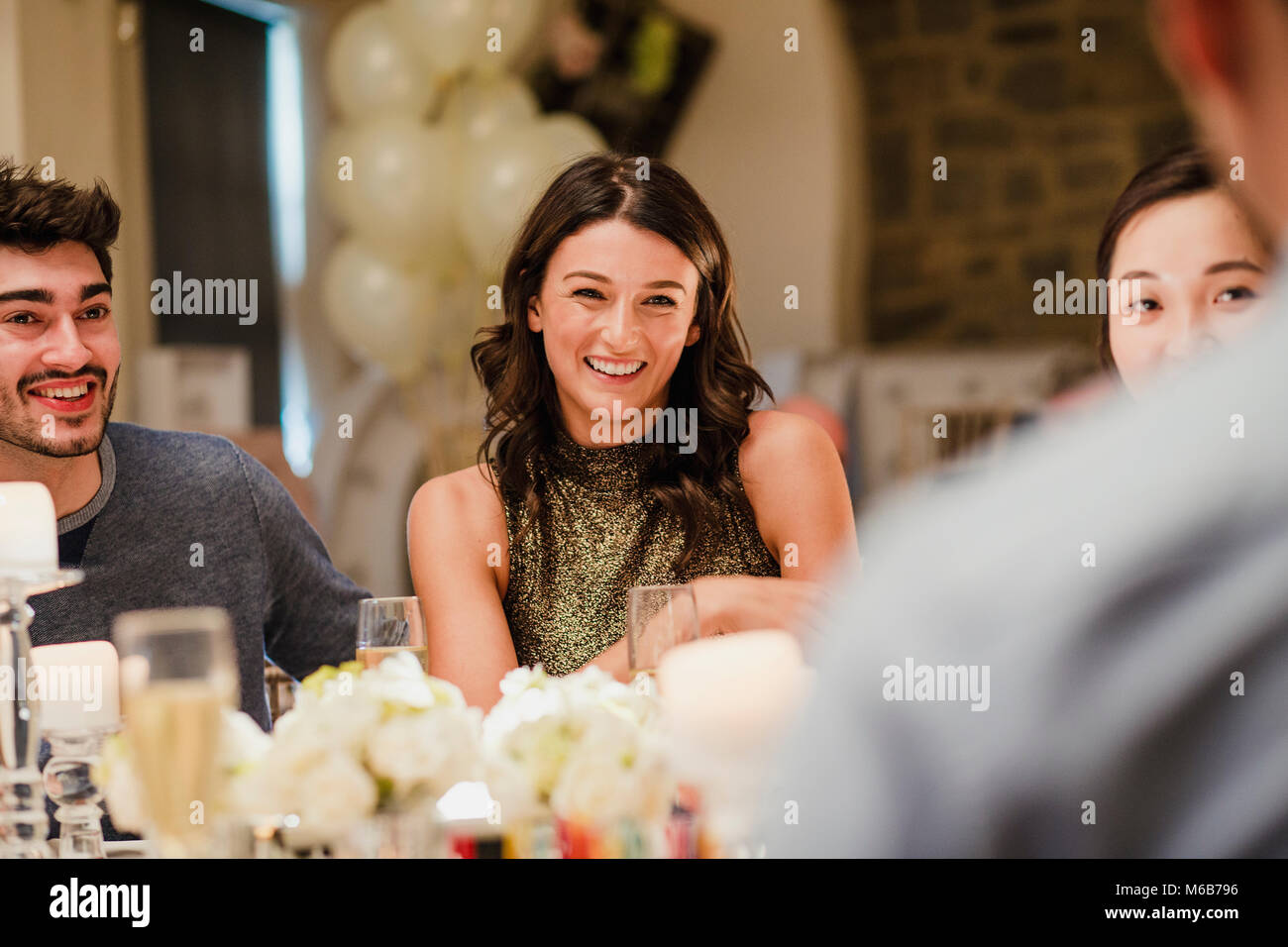Wedding guests are socialising at the dinner party. - Stock Image