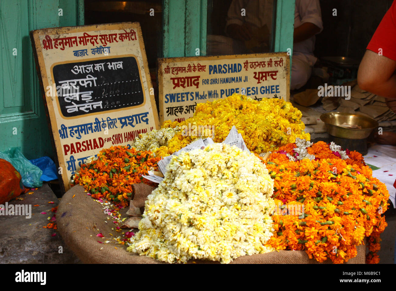 Bright yellow and orange flowers in a basket for sale for hinduist offerings in a market in Amritsar, India. - Stock Image