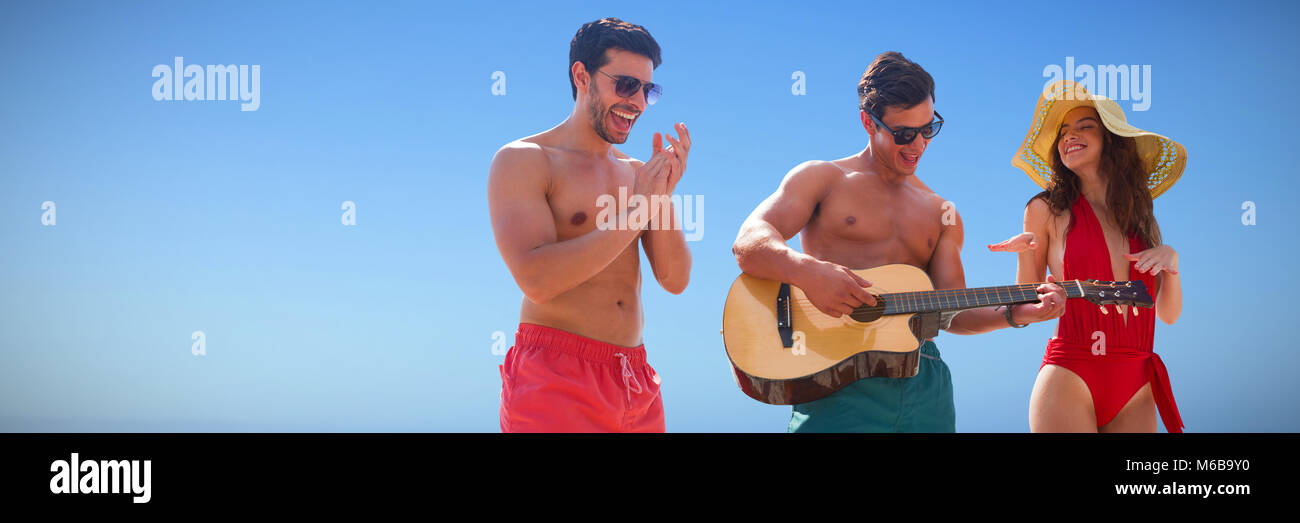 Composite image of friends playing music in swimwear - Stock Image