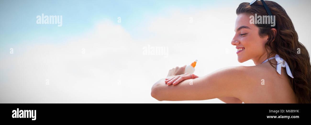 Composite image of beautiful women applying suncream - Stock Image