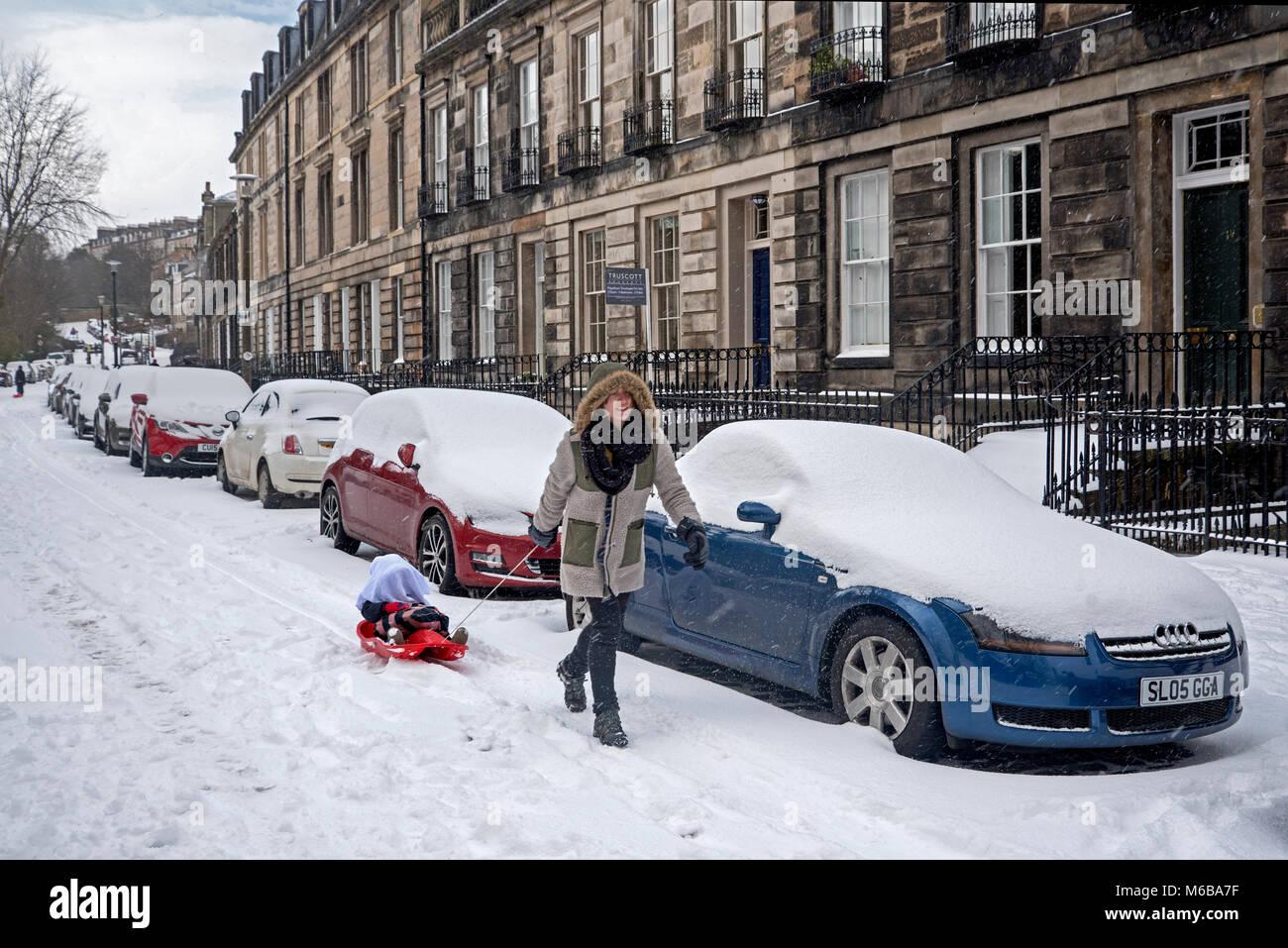 A woman pulling a child on a sledge through the snow in Stockbridge, Edinburgh. - Stock Image