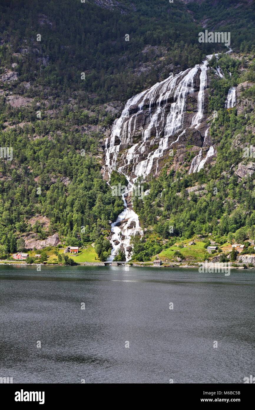 Norway fiord landscape - part of Hardanger Fjord called Sorfjord. Waterfall falling into the fiord. - Stock Image