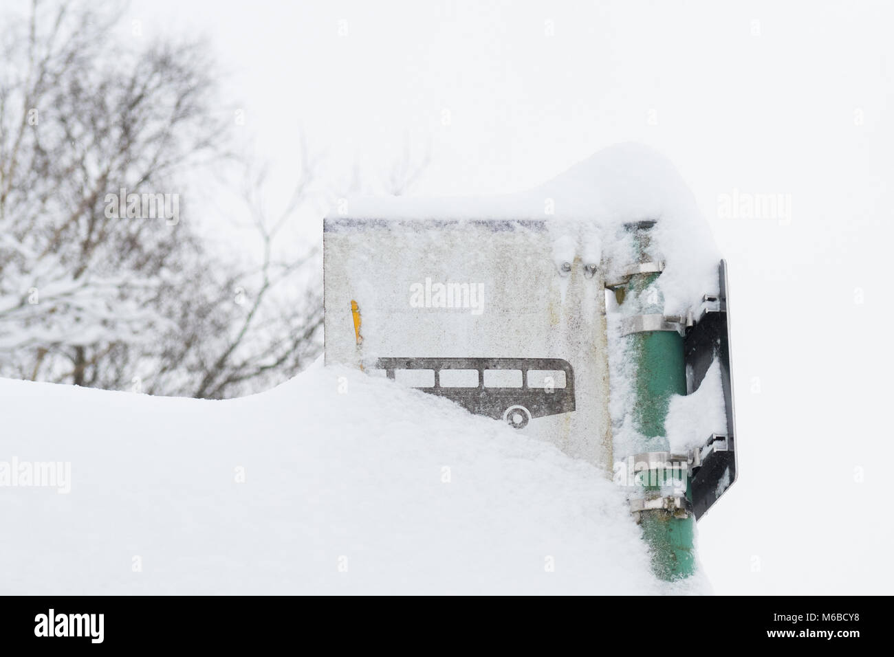 bus stop sign covered in snow - public transport in winter concept - Scotland, UK - Stock Image