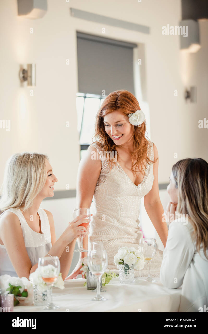 Beautiful bride is socialising with some of her friends who are guests at her wedding. They are sat at a table, Stock Photo