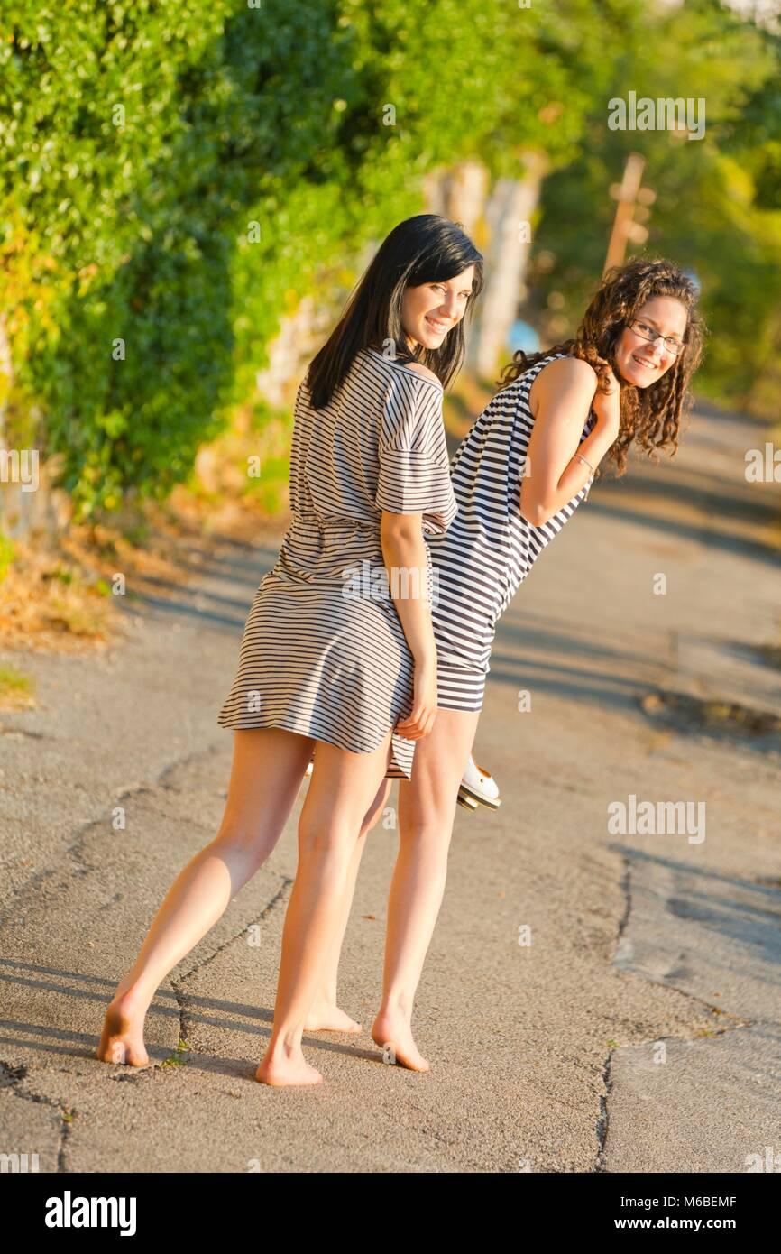 Friends bare feet barefoot walking to beach holding high heels shoes rear view from behind smiling looking at camera Stock Photo