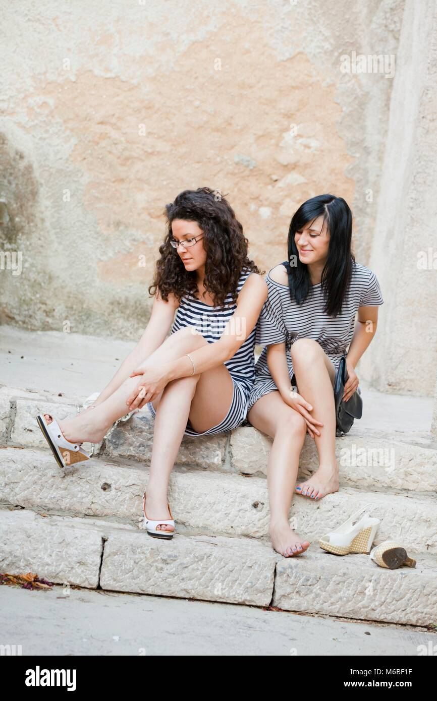 Sore legs in too tight high-heels friends relaxed alpfabet model-released release friendship - Stock Image