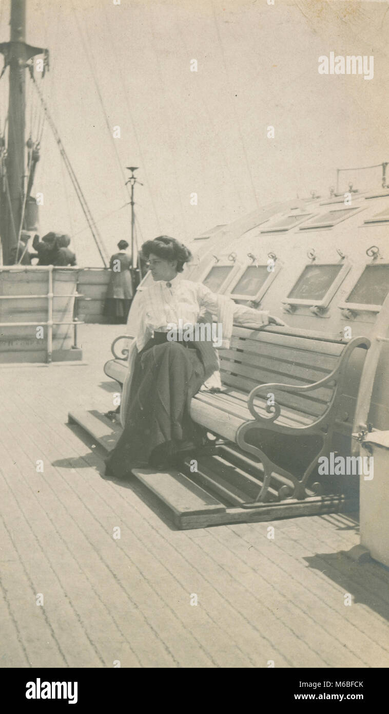 Antique c1900 photograph, woman seated on bench aboard a steamship. - Stock Image
