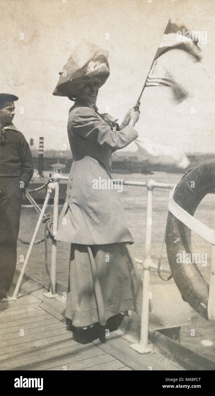 Antique c1900 photograph, woman waves flags from the deck of a steamship. The flags are American and possibly Netherlands - Stock Image