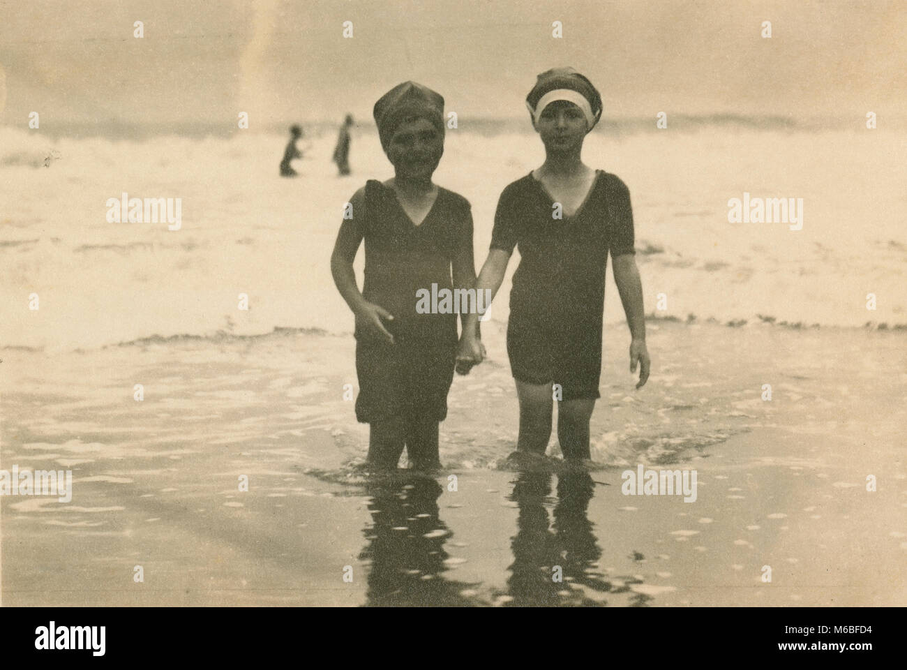 Antique c1900 photograph, two young children in Victorian bathing suits at the ocean. Location unknown, probably Stock Photo