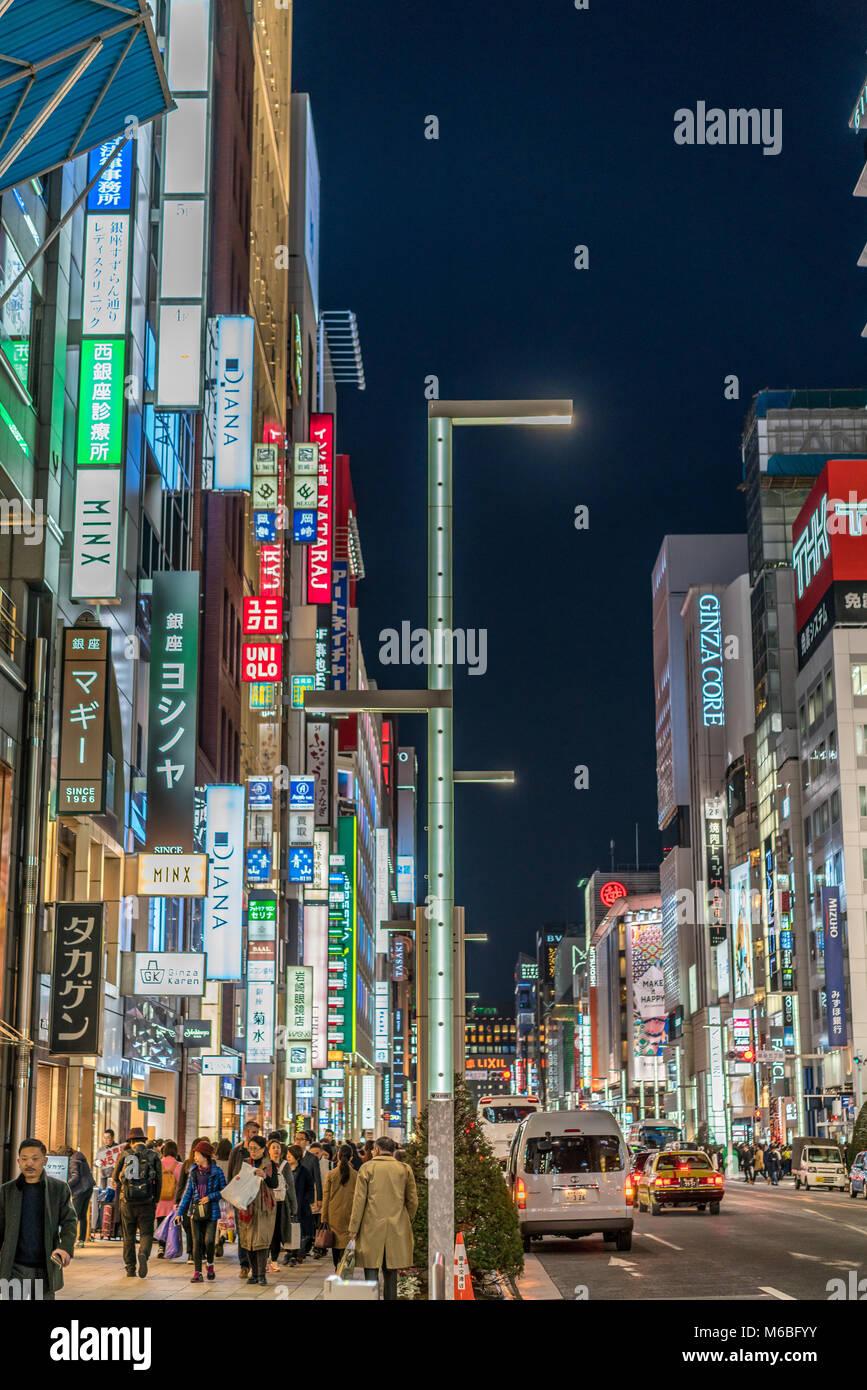 Ginza, Tokyo - December 2017 : Billboards, neon signs and People enjoying nightlife in crowded Chuo dori street Stock Photo