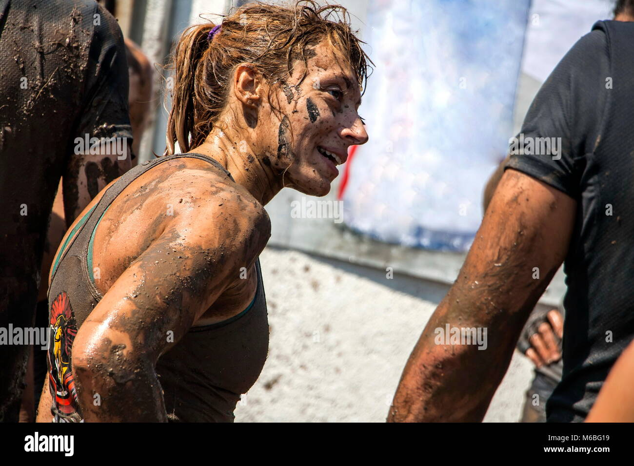 Young woman is smiling after overcoming the last challenge in an open sport challenge; concept of courage, determination - Stock Image