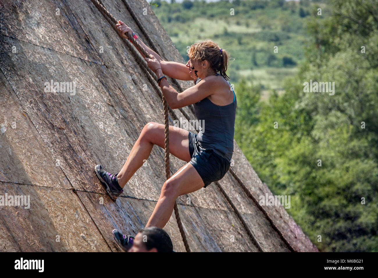 Young woman climbing a rope in extreme sport challenge; physical strength race; concept of courage, determination - Stock Image