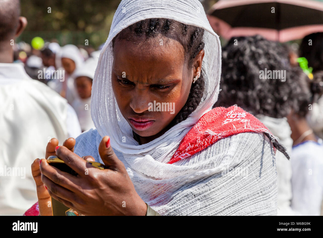 An Ethiopian Woman Looking With Concern At Her Mobile Phone, Addis Ababa, Ethiopia Stock Photo