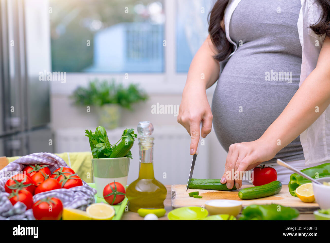 Pregnant woman cutting cucumber for fresh green salad, female prepares tasty organic dinner at home, healthy nutrition - Stock Image