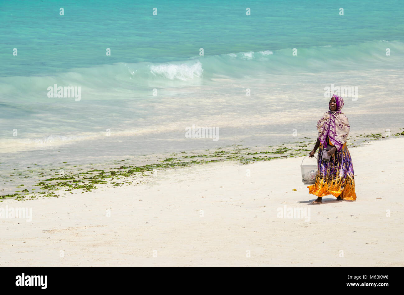 Zanzibar, Tanzania - December 4, 2014: Muslim woman with colorful clothes walking along the Nungwi beach. - Stock Image