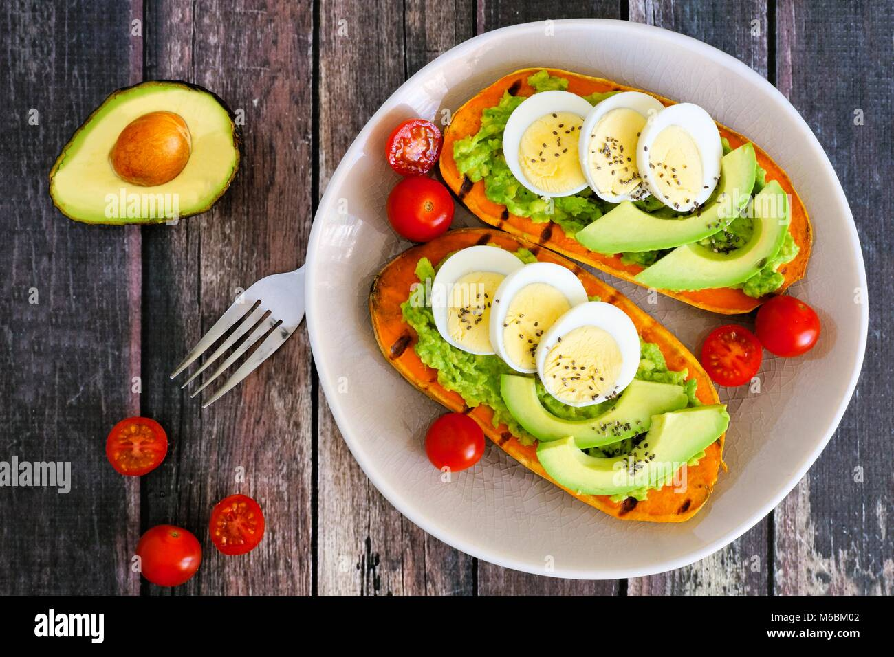 Sweet potato toasts with avocado, eggs and chia seeds on a plate. Top view on a dark wood background. Stock Photo
