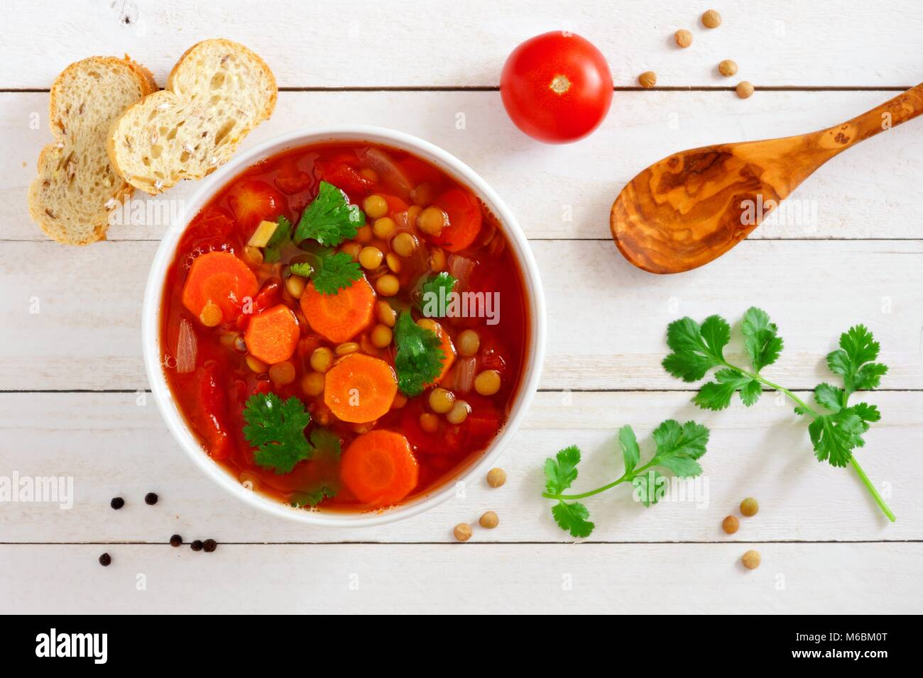 Homemade tomato, lentil soup, above scene on a white wood background Stock Photo