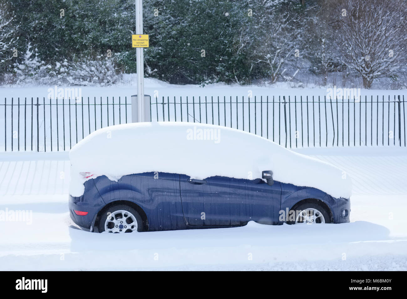 Parked car stuck covered in deep snow on road after heavy harsh winter snowfall unable to travel or transport - Stock Image