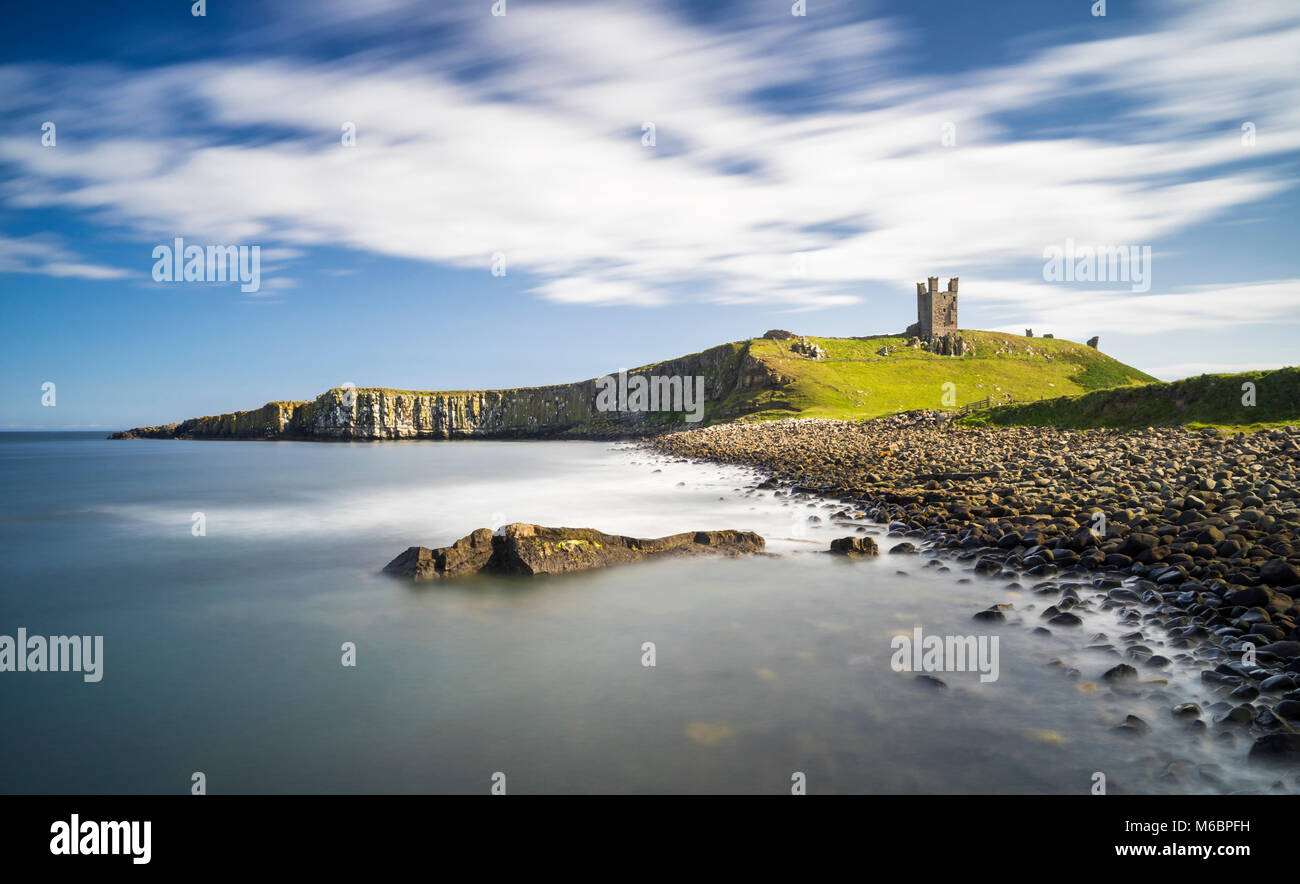 Dunstanburgh Castle from the north bay showing the Lilburn Tower and Greymare rocks, Northumberland, England - Stock Image