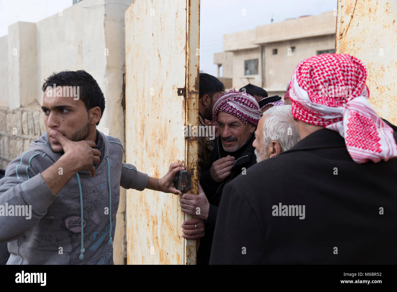 Mosul, Iraq. 8th December 2016 - Mosul locals try to convince their way into a barricaded school to seek shelter as fighting continues in the city of M Stock Photo