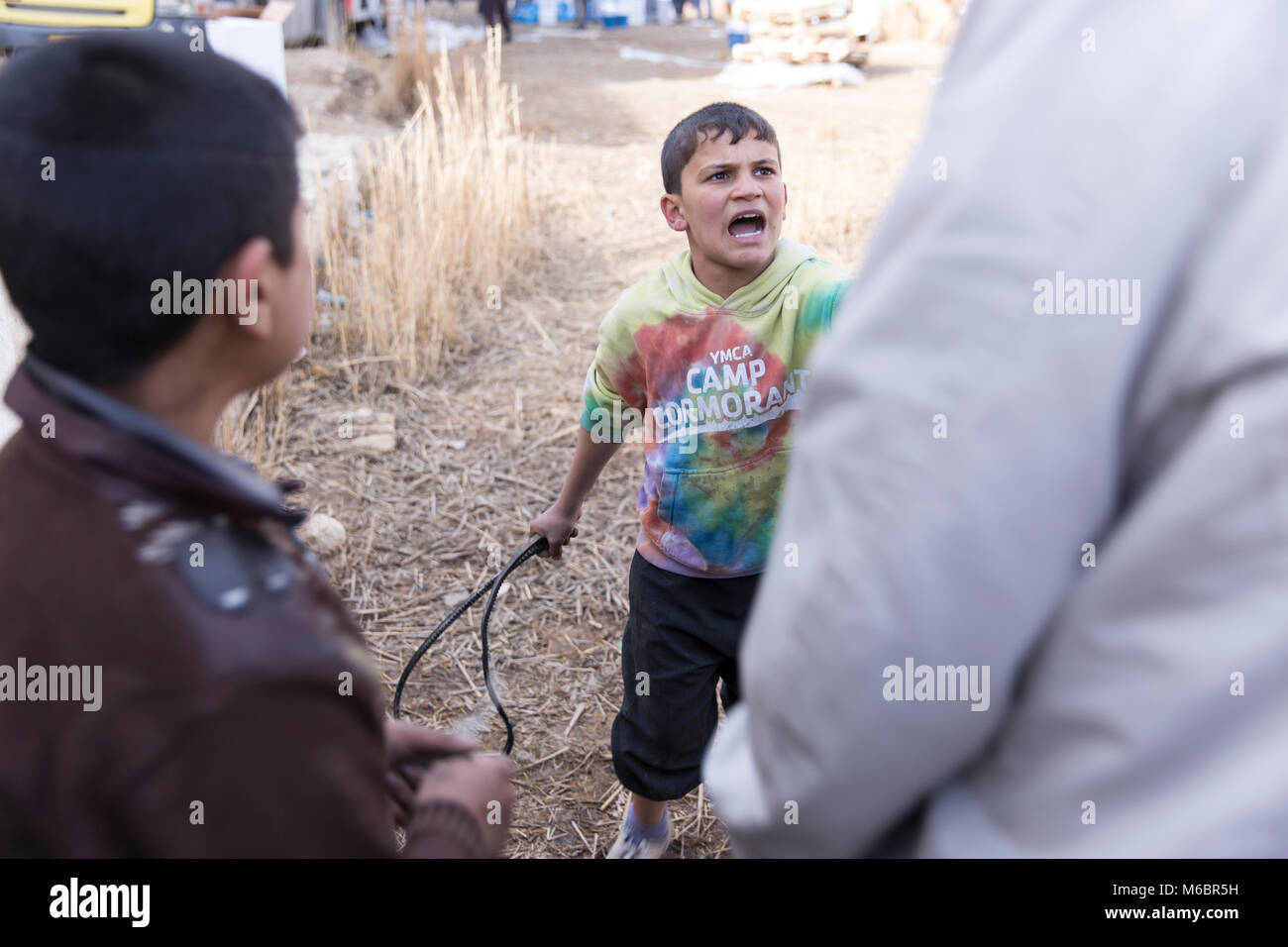 Mosul, Iraq. 8th December 2016 - A boy fights off tries to whip a man with a tyre tube to trying to steal aid during a United Nations distribution Stock Photo