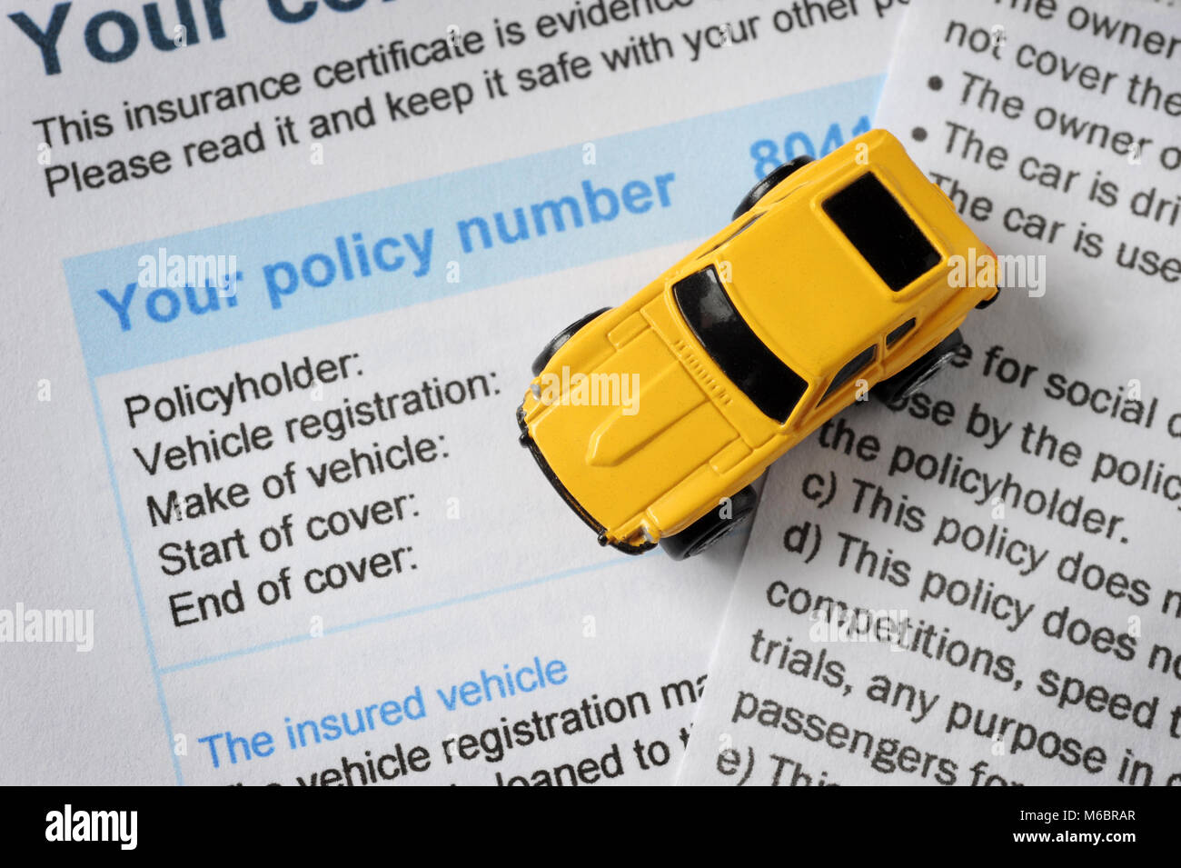 TOY CAR WITH CAR INSURANCE CERTIFICATE RE CLAIMS MOTORS POLICY RISING PREMIUMS COST ETC UK - Stock Image