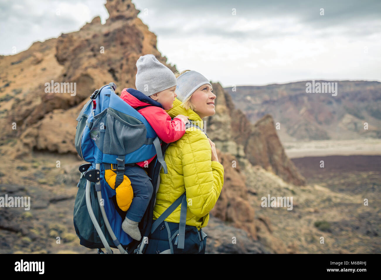 Family hike baby boy travelling in mother's backpack. Hiking adventure with child on autumn family trip in mountains. - Stock Image