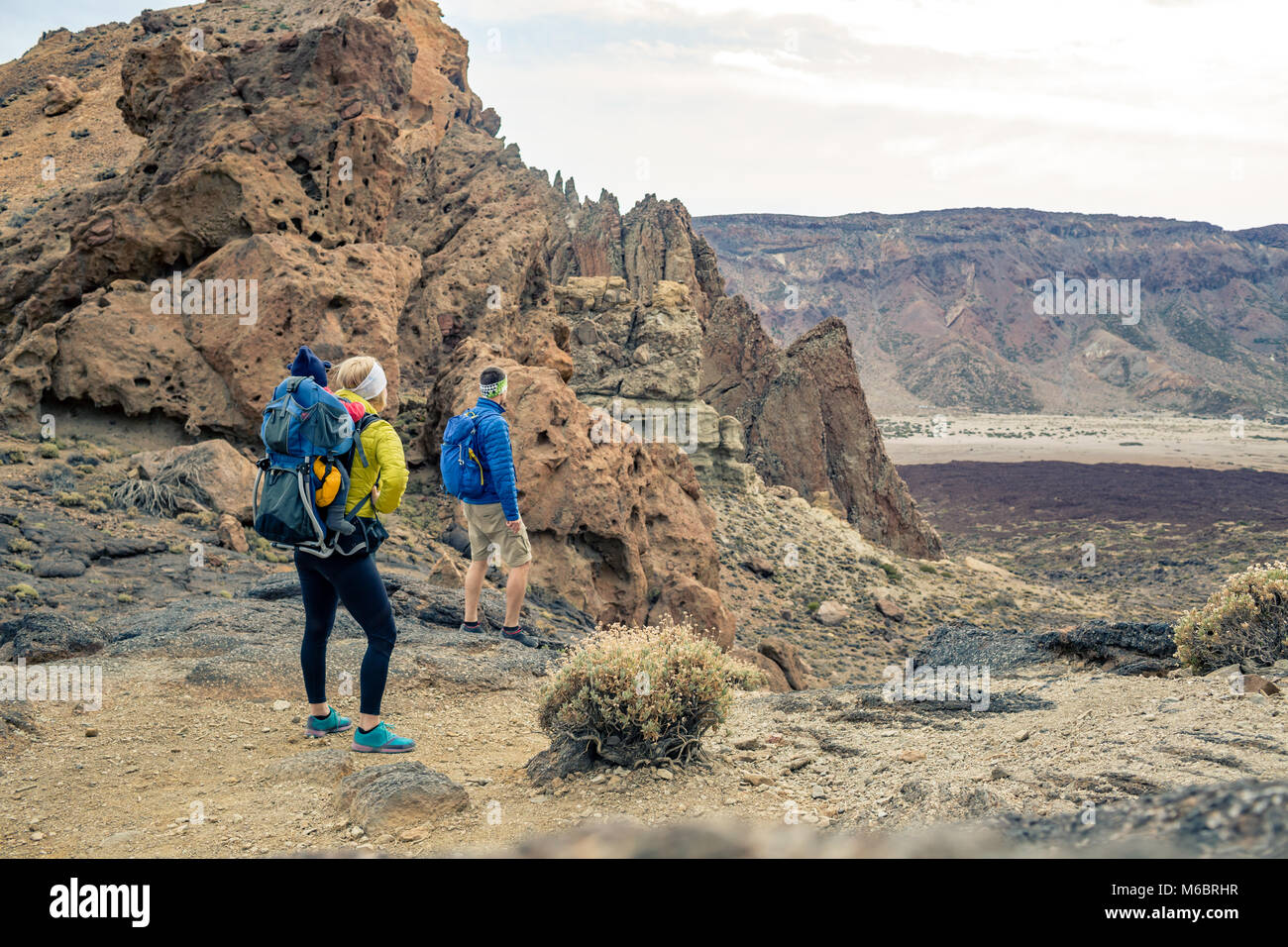Family hiking with baby boy travelling in backpack. Hiking adventure with child on autumn family trip in mountains. - Stock Image